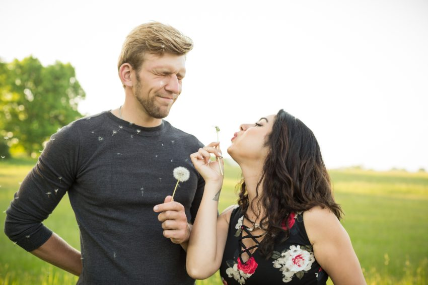 Cute couple blowing dandelions at each other